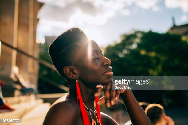 Young woman relaxing in the sun in the city.