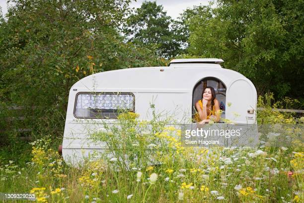 young woman relaxing inside camper trailer in idyllic meadow - camper trailer stock pictures, royalty-free photos & images