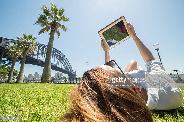 Young woman relaxing near Sydney habour bridge, uses digital tablet