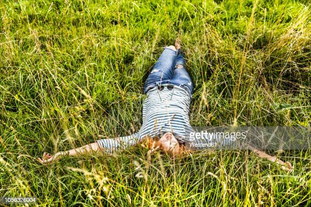 young woman relaxing on a meadow - einfaches leben stock-fotos und bilder