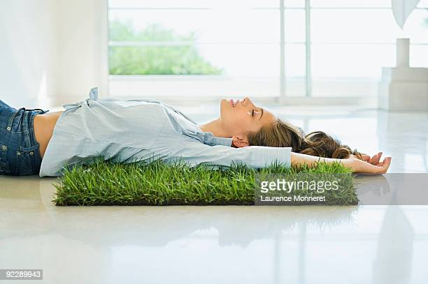 young woman relaxing on a square of grass - lying on back stock pictures, royalty-free photos & images