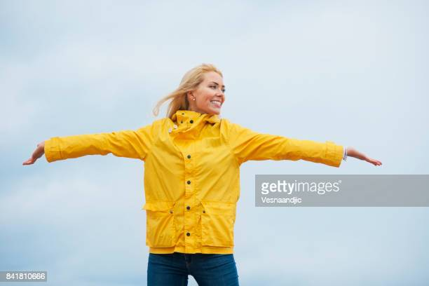 young woman relaxing on beach - raincoat stock photos and pictures