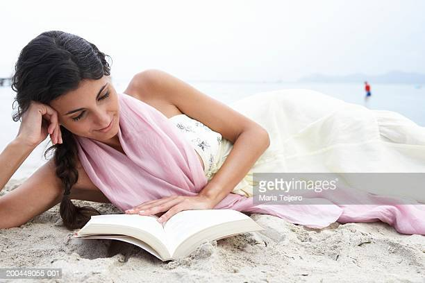 Young woman relaxing on beach, reading book