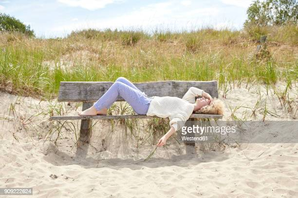Young woman relaxing on bench in beach dunes