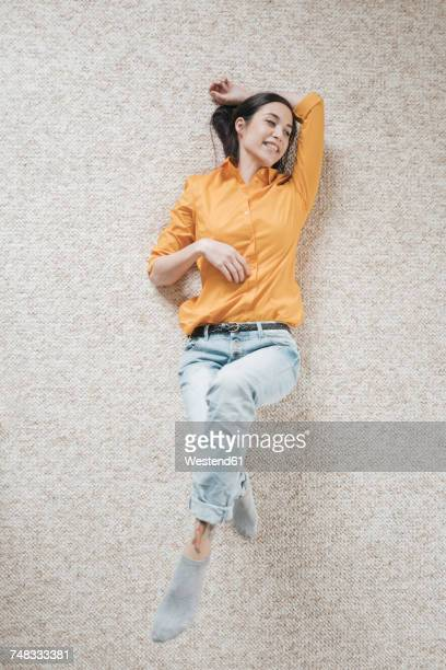 young woman relaxing on carpet - lying down foto e immagini stock