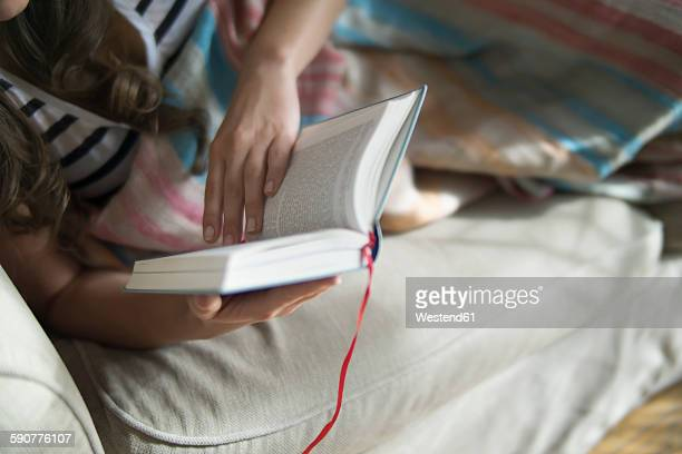 Young woman relaxing on couch, reading book