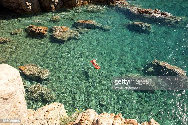 Young woman relaxing on floating mattress in cove-Italy