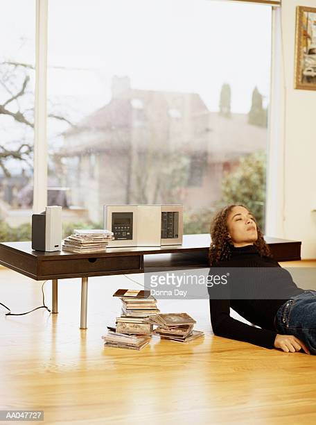 Young woman relaxing on floor, listening to music