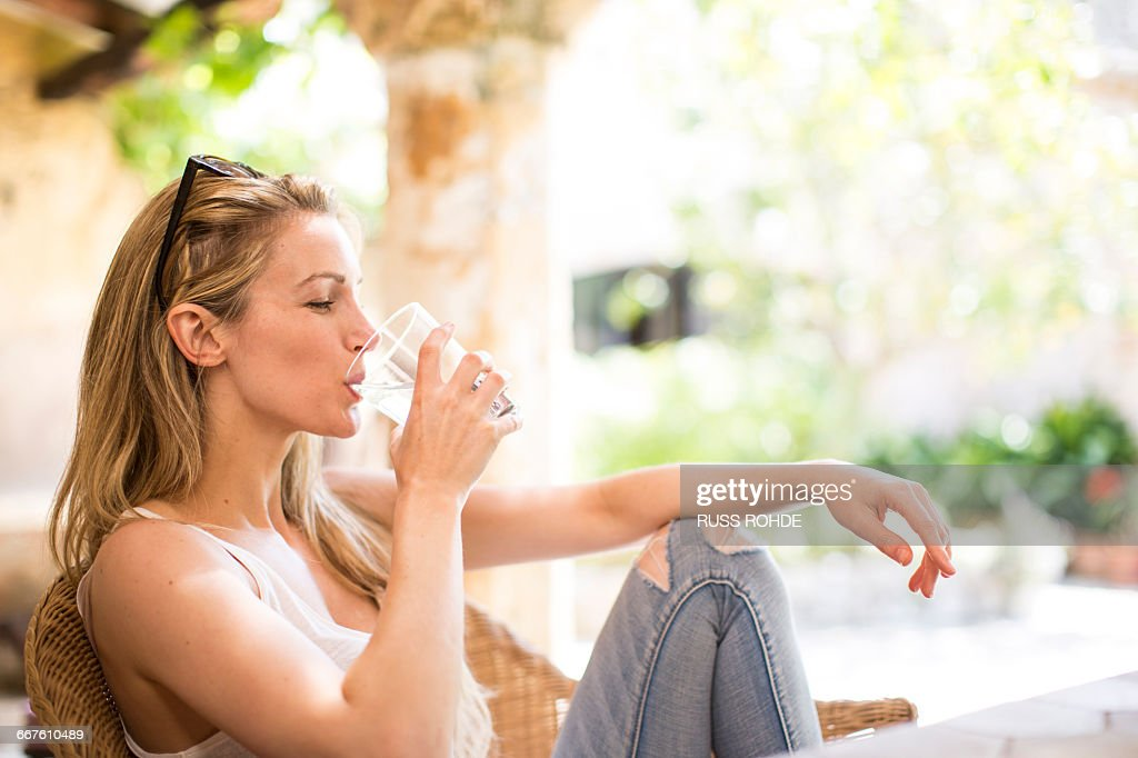 Young woman relaxing on garden patio drinking water : Stock Photo