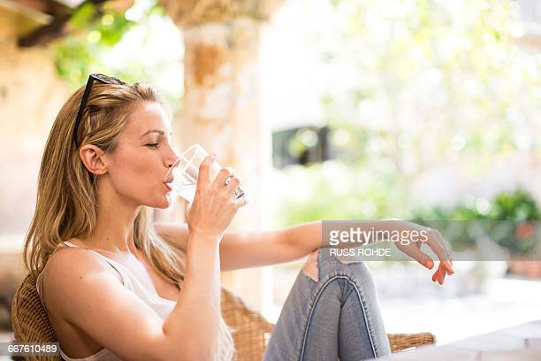 young woman relaxing on garden patio drinking water - trinkwasser stock-fotos und bilder