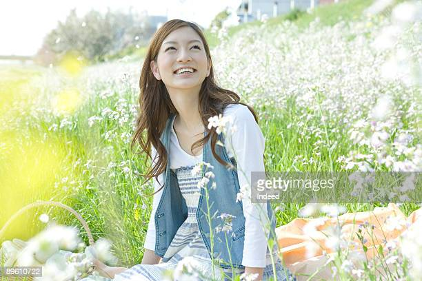 Young woman relaxing on grass field, looking up