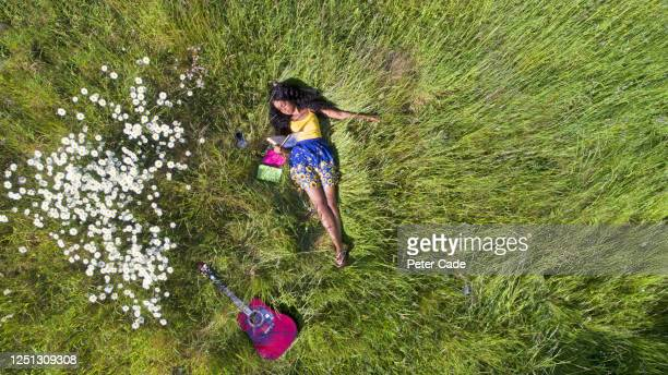 young woman relaxing on grass in summer - musician stock pictures, royalty-free photos & images