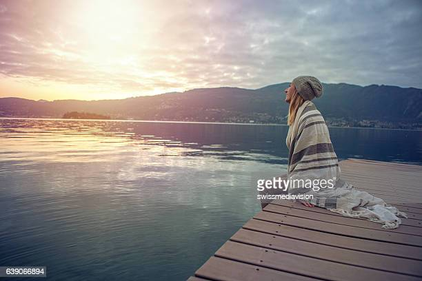 Young woman relaxing on jetty above lake, Italy
