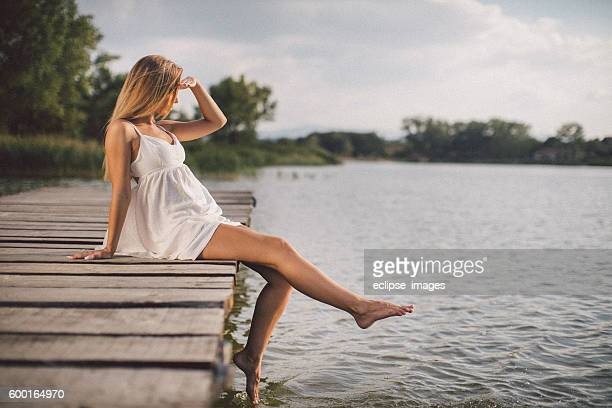 Young woman relaxing on jetty above lake