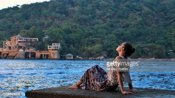 Young Woman Relaxing On Jetty Against Sea At Beach