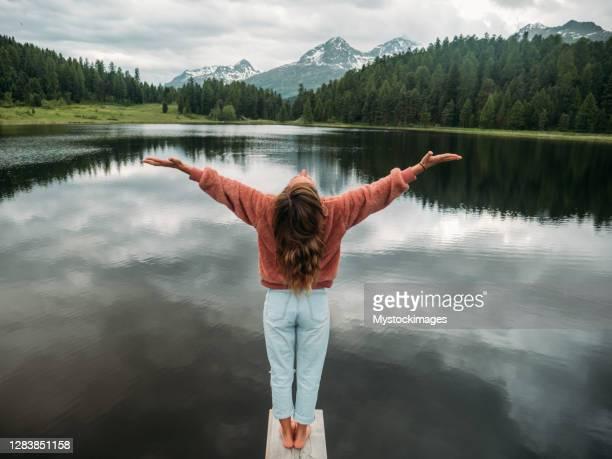 junge frau entspannen auf see pier umarmt die natur - offen allgemeine beschaffenheit stock-fotos und bilder