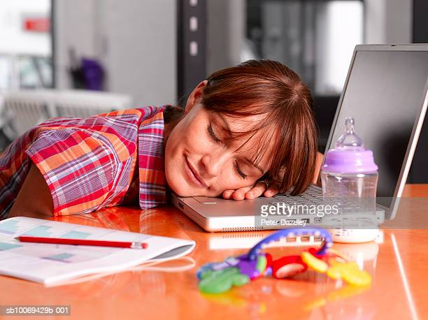 Young woman relaxing on laptop, eyes closed