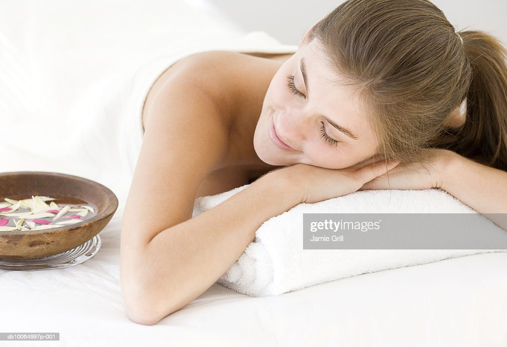 Young woman relaxing on massage table, smiling : Stock Photo