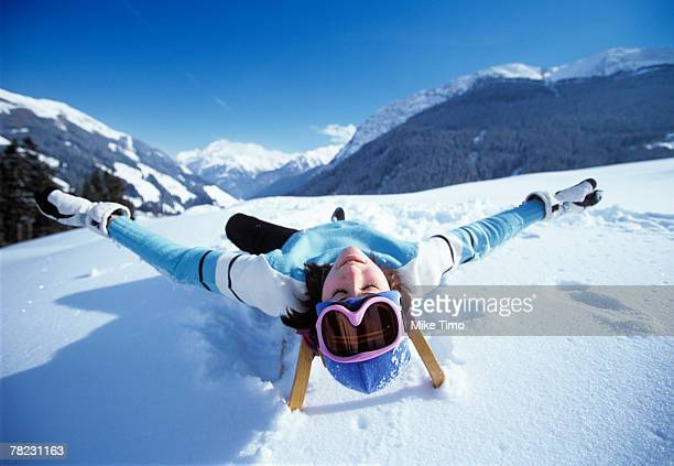 young woman relaxing on sledge in winter landscape