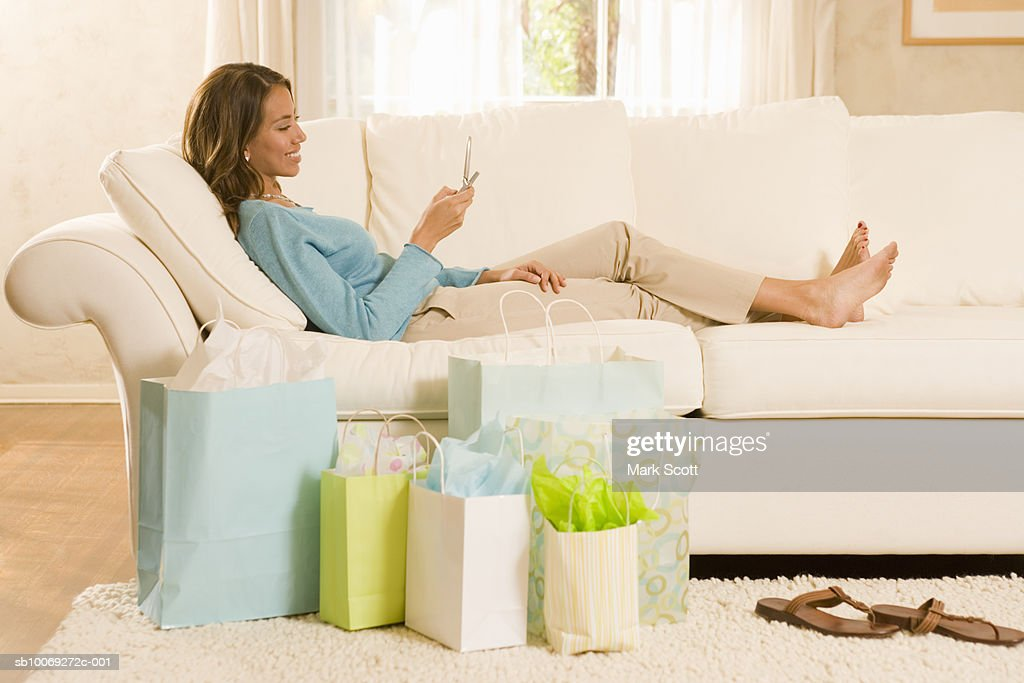 Young woman relaxing on sofa, shopping bags nearby : Stockfoto