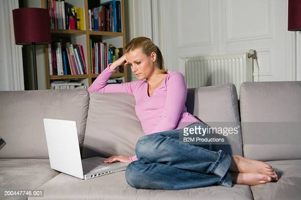 Young woman relaxing on sofa using laptop