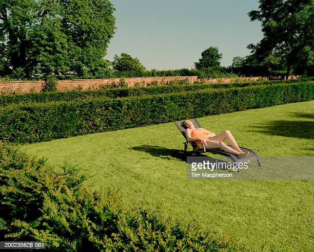Young woman relaxing on sun lounger in garden, laughing