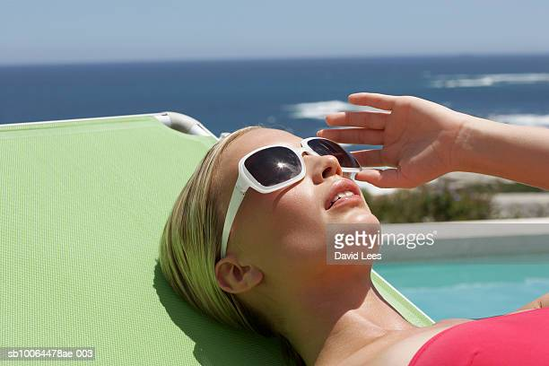 young woman relaxing on sunlounger beside swimming pool near ocean - liegen stock-fotos und bilder