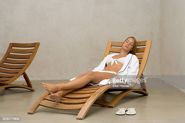 Young woman relaxing on sun-lounger