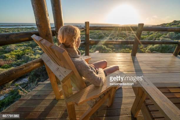 mujer joven relajante en terraza al atardecer - casita de campo fotografías e imágenes de stock