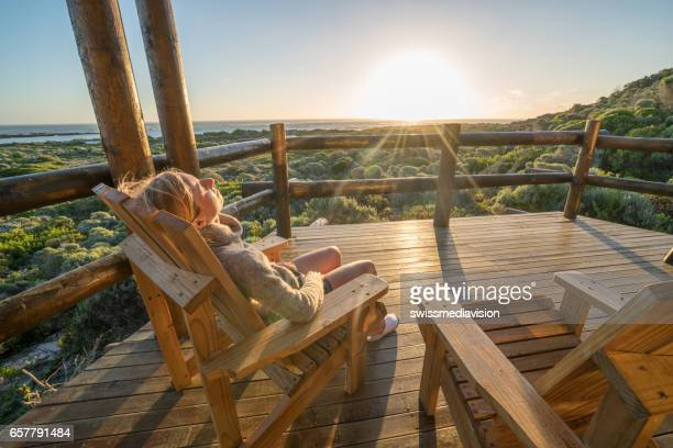 Young woman relaxing on terrace at sunset