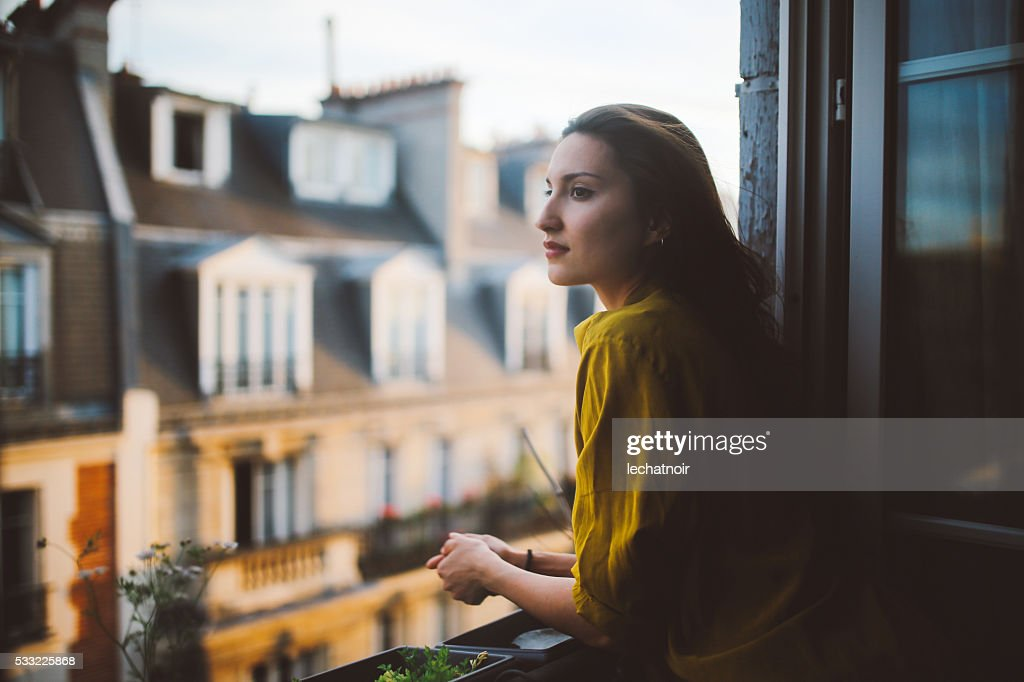 Young woman relaxing on the balcony of her Montmartre apartment : Stock Photo