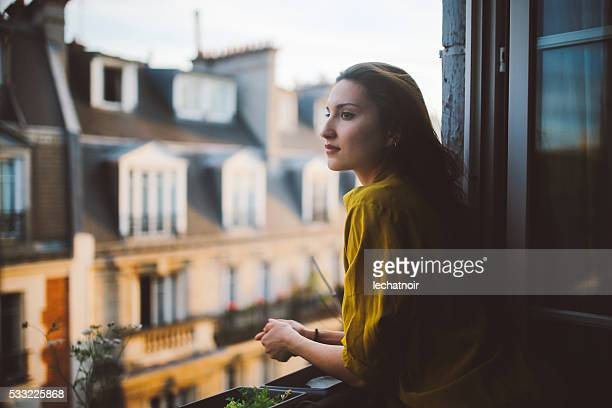 young woman relaxing on the balcony of her montmartre apartment - balcony stock pictures, royalty-free photos & images