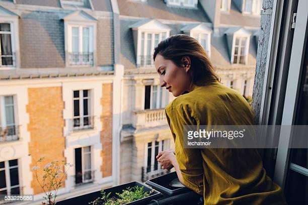 Junge Frau entspannt sich auf dem Balkon Ihres Pariser Appartment