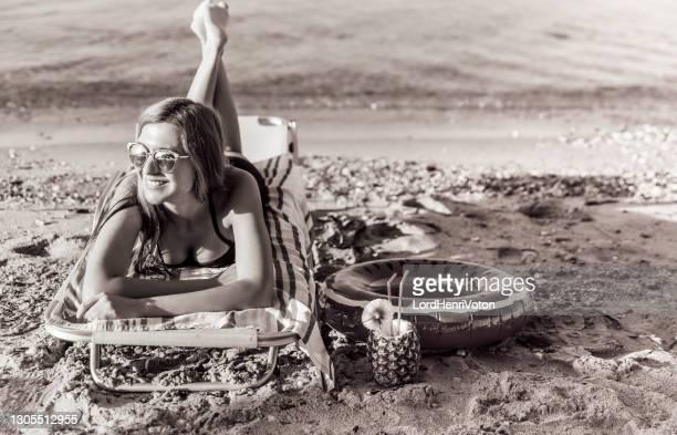 giovane donna che si rilassa sulla spiaggia - henri coste foto e immagini stock