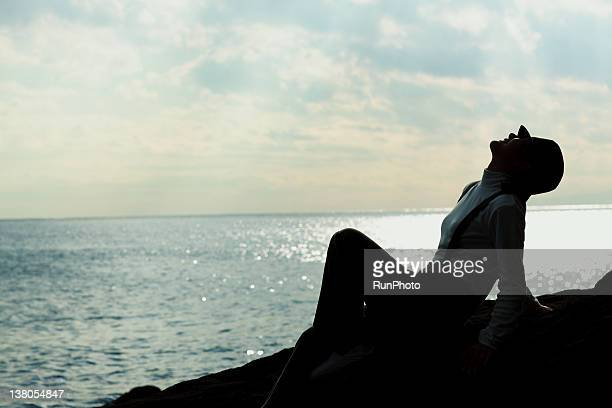 young woman relaxing on the rock near the sea - 頭をそらす ストックフォトと画像
