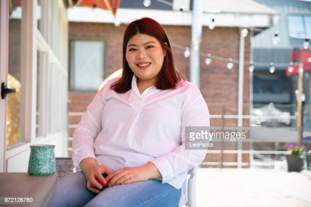 young woman relaxing outdoor on the terrace - fat asian woman stock pictures, royalty-free photos & images