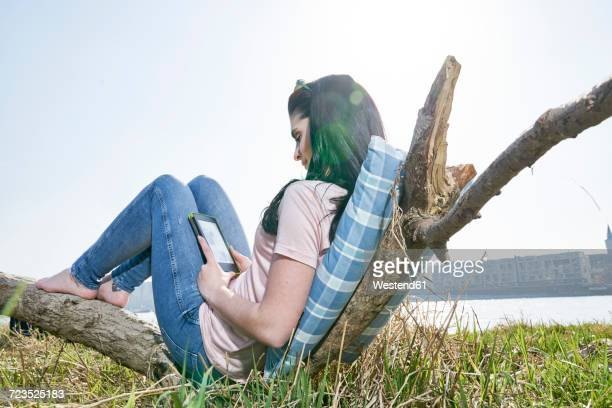 Young woman relaxing outdoors using tablet
