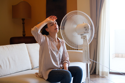 Young woman relaxing under the air fan at home 953794730
