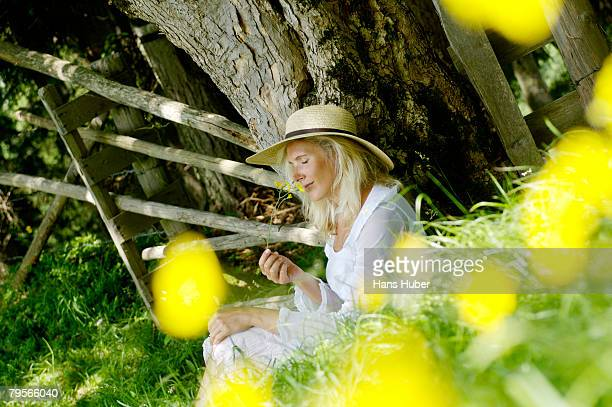 young woman relaxing under tree - sun hat stock pictures, royalty-free photos & images