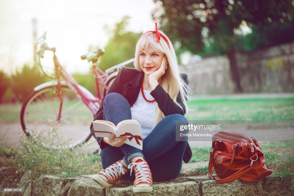 Young woman relaxing while reading a book at the park : Stock-Foto