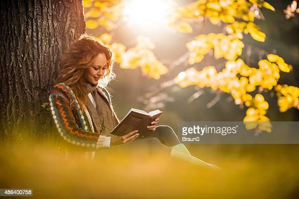Mujer joven relajante mientras lee un libro en otoño.