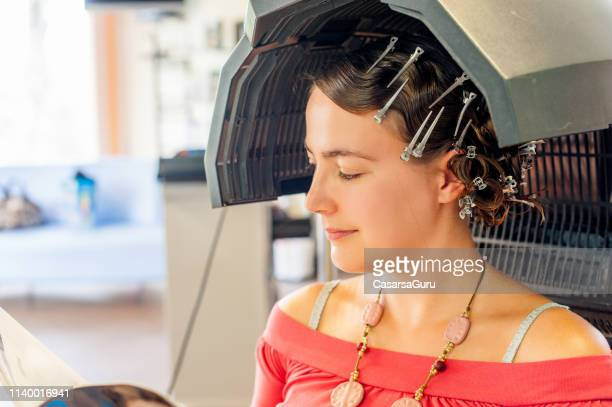 young woman relaxing while waiting under the dryer in the hair salon - permed hair stock photos and pictures