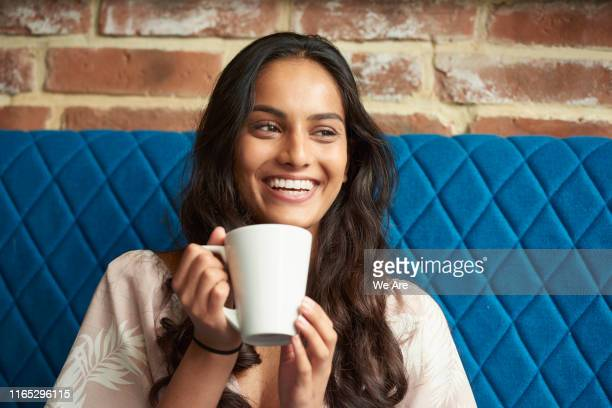 young woman relaxing with a cup of coffee - pretty woman stock pictures, royalty-free photos & images