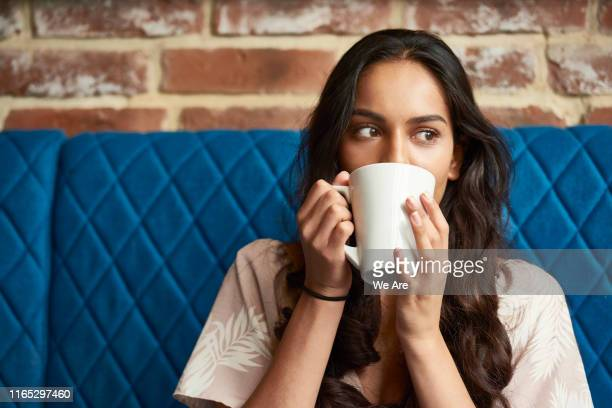 young woman relaxing with a cup of coffee - indulgence stock pictures, royalty-free photos & images