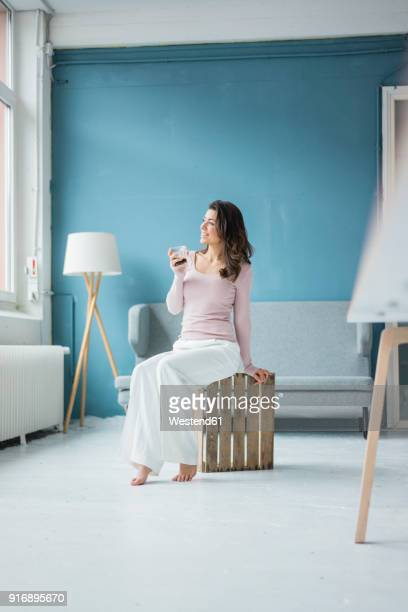 young woman relaxing with glass of coffee in a loft looking out of window - sitzen stock-fotos und bilder