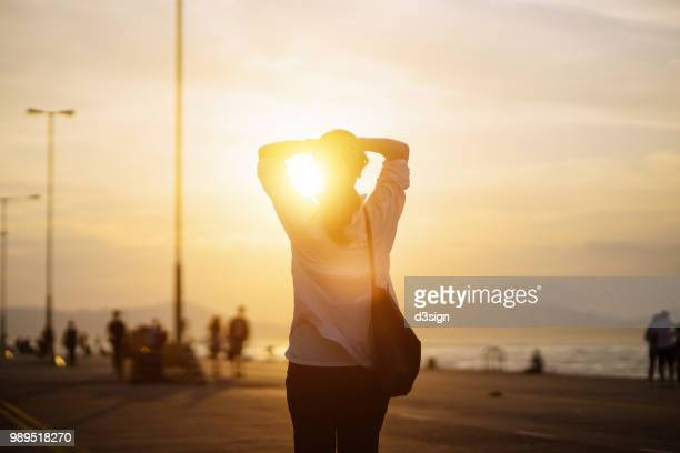 Young woman relaxing with hands behind head by the pier and enjoying the beautiful sunset and warmth of sunlight