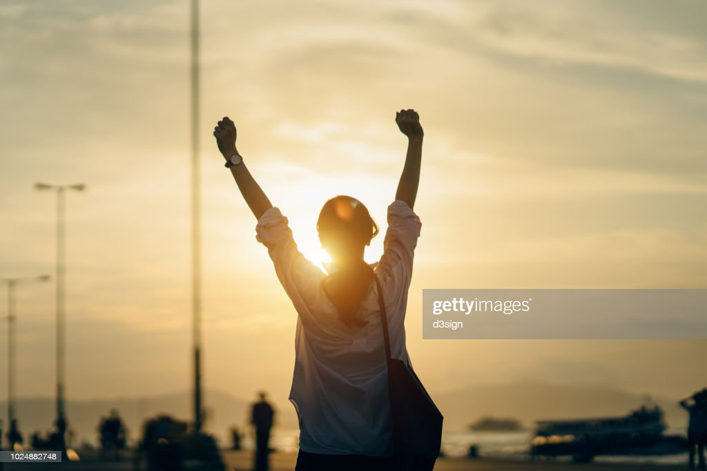 Young woman relaxing with hands in the air by the pier and enjoying the beautiful sunset and warmth of sunlight : Stock Photo