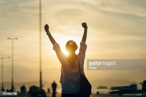 young woman relaxing with hands in the air by the pier and enjoying the beautiful sunset and warmth of sunlight - emoción positiva fotografías e imágenes de stock
