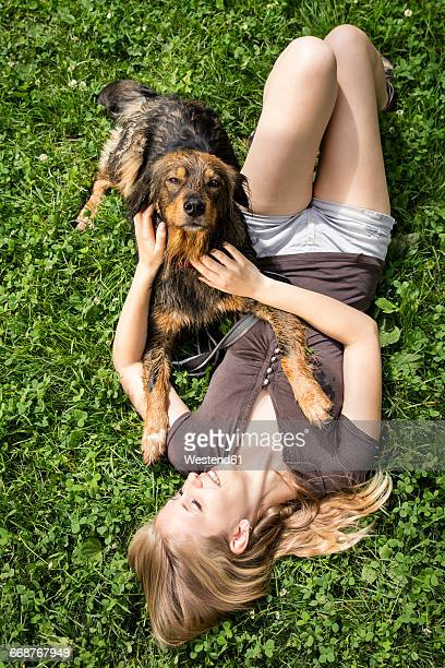 Young woman relaxing with her dog on a meadow