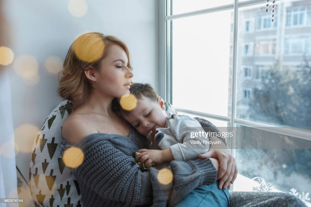 Young woman relaxing with son by window at home : Stock Photo
